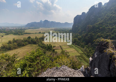 Beautiful view of fields and karst limestone mountains from above near Vang Vieng, Vientiane Province, Laos, on a sunny day. - Stock Photo