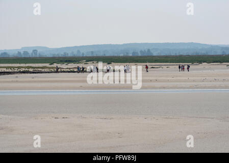 A group of people crossing the Somme estuary on foot at low tide. - Stock Photo