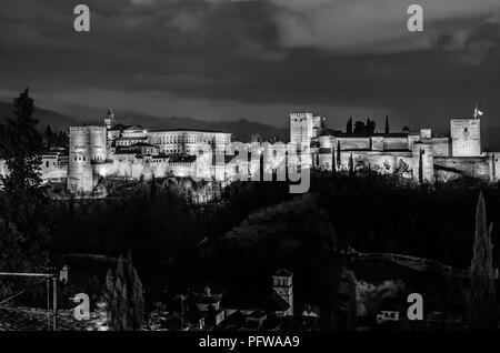 Cityscape of Granada, southern Spain, with the Alhambra Palace in the background, night view, black and white image - Stock Photo