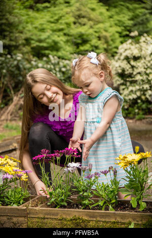 12 and 1 year old cousins admiring the flowers (MR) - Stock Photo
