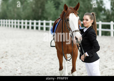 Portrait of rider elegant woman talking to her horse outside. jockey and brown horse - Stock Photo