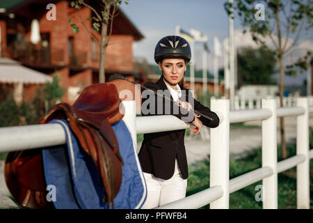 portrait of elegant rider woman in helmet with whip stands near fence of manege after training at sunset - Stock Photo