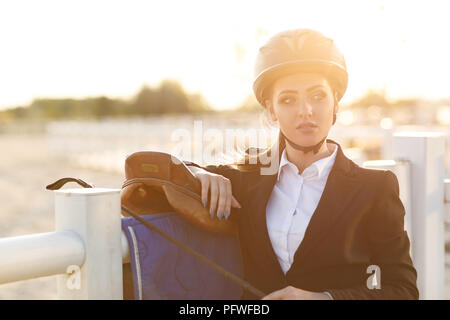 portrait of elegant rider woman in helmet with whip stands near fence of arena after training at sunset. soft light - Stock Photo