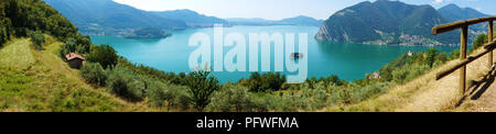Panoramic view of mountain lake with island in the middle. Panorama from Monte Isola Island with Lake Iseo, Italy. Italian landscape. Island on lake. - Stock Photo