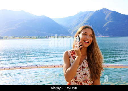Cheerful young lady with floral dress outdoor standing near lake and talking by her phone. Copy space. - Stock Photo