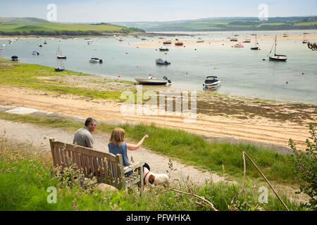 UK, Cornwall, Rock, couple sat on waterfront bench beside River Camel - Stock Photo