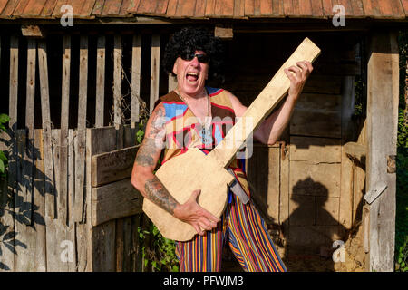 spoof portrait of older male wearing wig sunglasses bright clothing and medallion while playing a fake guitar mid life crisis concept hungary - Stock Photo