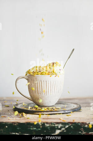 Pistachio ice cream in mug with nuts falling from above - Stock Photo