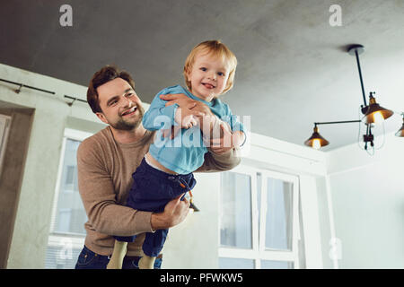 The father plays with his son in a superhero, a pilot in the roo - Stock Photo