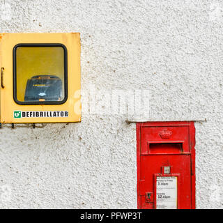 DEFIBRILLATOR AND RED LETTER BOX ON A WHITE WALL - Stock Photo