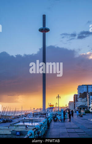 Brighton promenade at sunset with the moving viewing tower in the centre the promenade is very busy a pride flag is flying in the background the sky i - Stock Photo