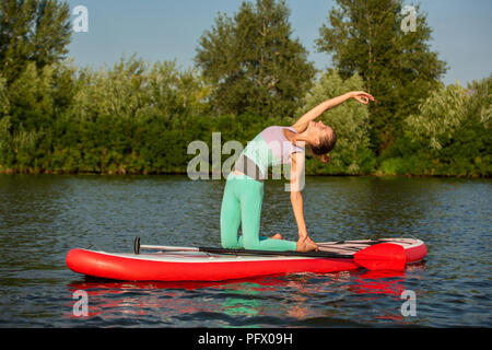 Woman practicing yoga on the paddle board in the morning - Stock Photo