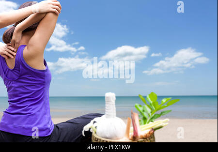Asian woman having Thaj massage on the beach with herb  - Stock Photo