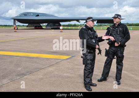 Armed police guard a Northrop Grumman B-2 Spirit 21068 Spirit of New York on display at the Royal International Air Tattoo RIAT RAF Fairford Cotswolds - Stock Photo