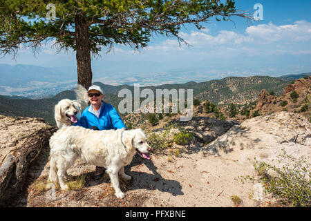 Female hiker resting with two white Golden Retriever dogs; high vantage point view of forest fire smoke; Salida & Arkansas River Valley from The Crate - Stock Photo