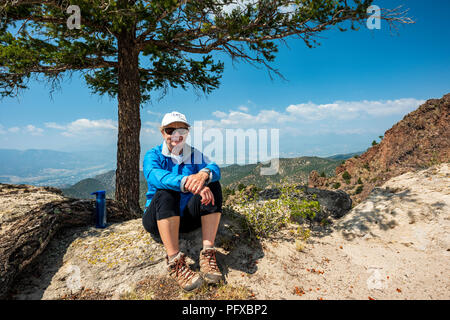 Female hiker resting; high vantage point view of forest fire smoke; Salida & Arkansas River Valley from The Crater; USA - Stock Photo