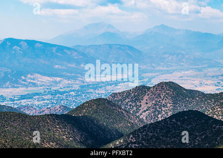 Forest fire smoke; high vantage point view of Salida; Arkansas River Valley & Rocky Mountains beyond from The Crater; USA - Stock Photo