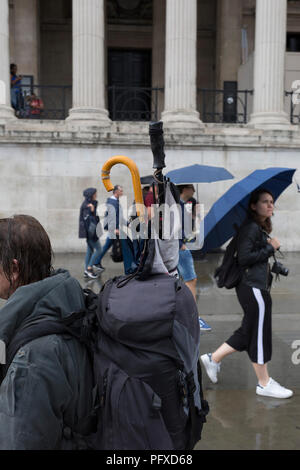 Pedestrians and umbrellas during a sudden downpour in Trafalgar Square, on 13th August 2018, in London, England. - Stock Photo