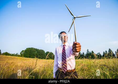 An African American man holding a small model of a wind turbine. Concept of green energy / green business - Stock Photo