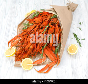 Cooked crayfish and crab claws with lemon are decorated in the form of a bouquet - Stock Photo