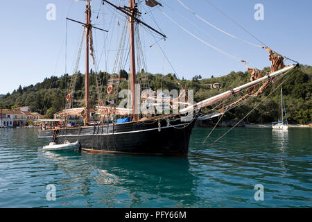 The harbour at Lakka, Paxos, Greece in early morning, with the topsail schooner Rhea at anchor - Stock Photo