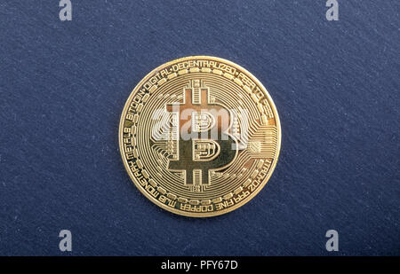 golden bitcoin in a woman hand, symbol of a crypto-currency - Stock Photo