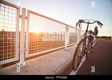 Lonely bike on the roadside. Road with sunset in the background - Stock Photo