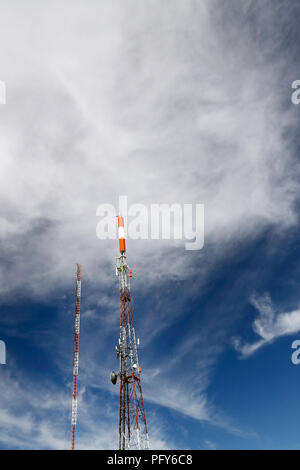 Wide view of two communication antennas against a blue mountain sky with white clouds - Stock Photo