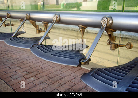 Silver metalic designed seats in the bus stop, summer - Stock Photo