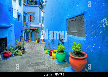 Scenic view of narrow street with colorful flowerpots in old medina of blue town Chefchaouen. Morocco, North Africa - Stock Photo
