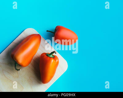 Pepper in top view Photo template with copy space Three big sweet red peppers are lying on cutting board on a blue background - Stock Photo