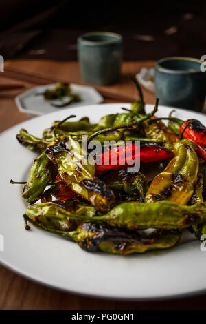 Charred green and red shishito peppers with sweet togarashi spice served on a round white plate. - Stock Photo