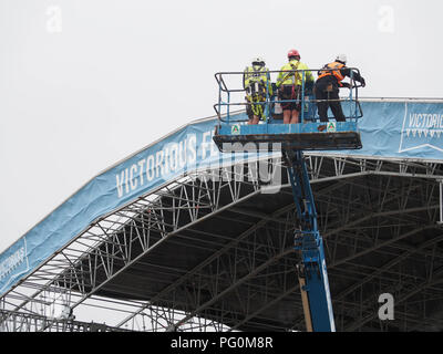 Stage crew errcting a stage for a music festival using a cherry picker - Stock Photo