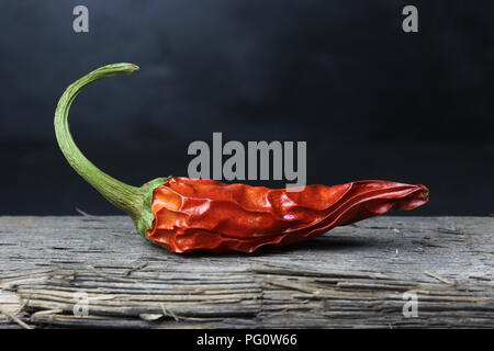 dried chili peppers on wood against a dark background - Stock Photo