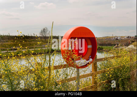 Orange Lifebuoy attached to wooden railings overlooking a lake in Hertfordshire - Stock Photo