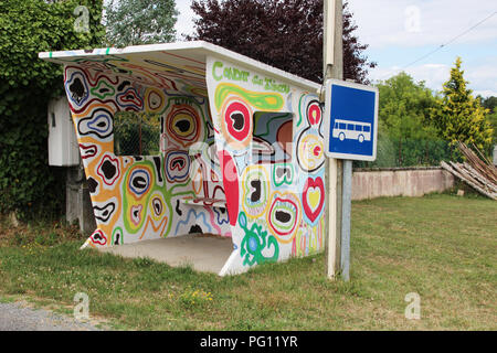 Country bus shelter hand painted in pyschedelic graffiti by local schoolchildren in village in France - Stock Photo