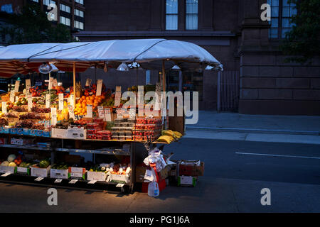 Outside fruit and vegetable stand at nighttime in New York City - Stock Photo