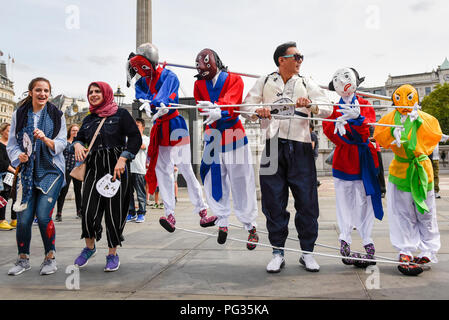London UK.  23 August 2018.  Members of The Crown 'Dongrak Dancing' troupe from Korea stage an impromptu street performance in Trafalgar Square.  Dongrak Dancing is translated as 'Dancing Together'.  Dancers are connected to mannequins giving the impression of several people dancing together.  The troupe has recently performed at the Edinburgh International Festival.  Credit: Stephen Chung / Alamy Live News - Stock Photo