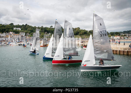 Lyme Regis, Dorset UK 23rd August 2018. Merlin Class dingies sail right into a crowded harbour  in gusty winds after a days racing competition at the National Sailing Championships. Credit: Julian Eales/Alamy Live News - Stock Photo
