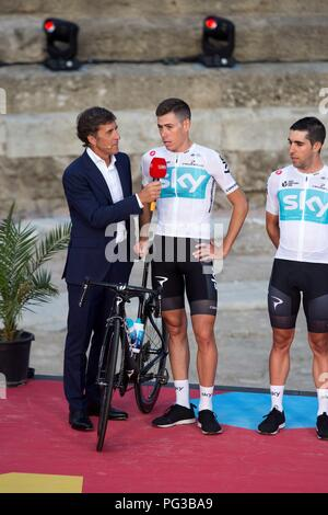 Malaga, Spain. 24th August, 2018. Skyr cycling team's Spanish cyclist David de la Cruz (C) talks to Spanish sports commentator, former cyclist Pedro Delgado (L), on the stage at Roman Theater during the presentation of the cycling teams competing in La Vuelta cycling tour in Malaga, southern Spain, 23 August 2018 (issued on 24 August 2018). La Vuelta runs from 25 August to 16 September. EFE/ Daniel Perez Credit: EFE News Agency/Alamy Live News - Stock Photo