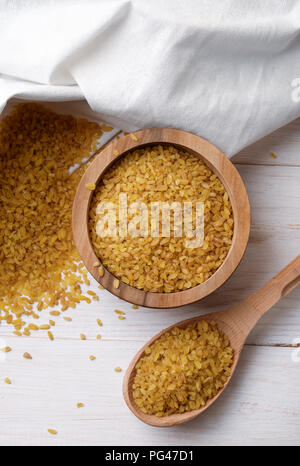 Top view of dry bulgur wheat in  bowl and spoon on  wooden background. - Stock Photo