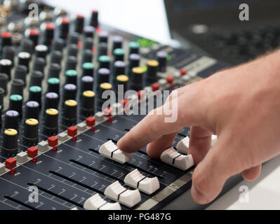Audio engineer working on mixing console in music studio - Stock Photo