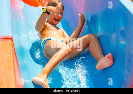 A happy boy on water slide in a swimming pool having fun during summer vacation in a beautiful aqua park. A boy slithering down the water slide and making splashes. - Stock Photo