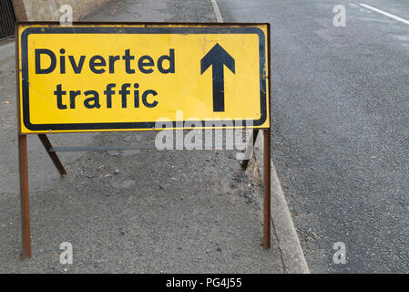 Old, weathered, black and yellow diverted traffic road safety sign on the side of the road. Black text on yellow background with arrow forward - Stock Photo