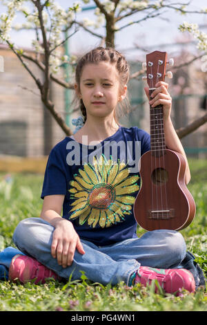 A little girl playing ukulele in the garden - Stock Photo