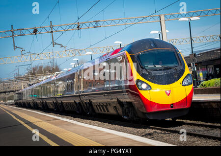Virgin Trains pendolino class 390 electric high speed train arriving at a railway station on the Abbey Line, Hertfordshire, UK. - Stock Photo