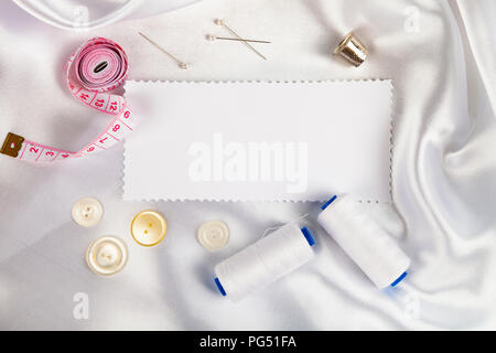 Sewing accessories and a note on white satin fabric. White satin fabric, thread, thimble, pins and measuring tape.
