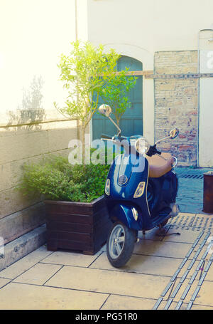 Antalya, Turkey 10 May 2018. Blue hipsters scooter on a street next to a tub with a little tree. - Stock Photo