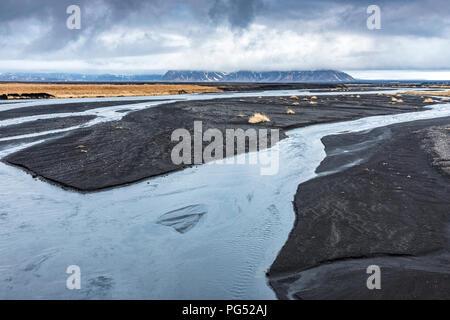 River delta in black desert near Lomagnupur in Iceland - Stock Photo