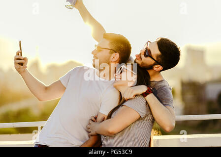 Friends taking selfies outdoors in the terrace at sunset with a warm light in the background - Stock Photo